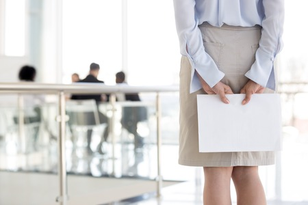 Close up of female employee standing in hallway holding documents, feeling worried before entering boardroom, nervous woman worker waiting being anxious before presentation or speech at briefing