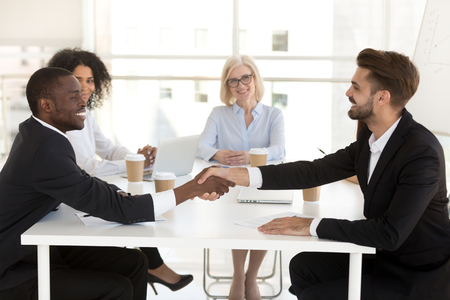 Smiling diverse business partners shake hand closing deal at office meeting, multiethnic excited businessmen handshake making agreement, starting cooperation after successful negotiation