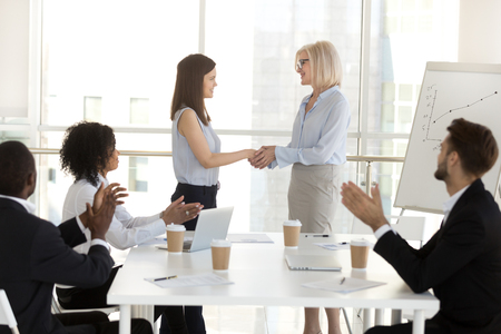 Mature businesswoman handshake millennial female employee congratulating with promotion or employment, diverse colleagues applaud watching boss shake hand of hired successful intern