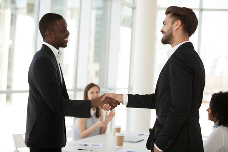 Excited diverse partners handshake after successful business briefing in office, boss shake hand of colleague congratulating with promotion, multiethnic businessmen closing deal at meeting