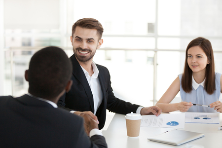 Smiling Caucasian man handshake black colleague getting acquainted at office meeting, multiethnic employees shake hands greeting or introducing at briefing, male worker congratulate coworker Stockfoto