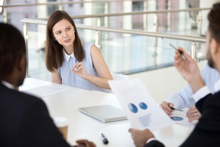 Young female employee talk on paperwork issues during company meeting with colleagues, millennial woman share thoughts and ideas on document or report, discussing with coworkers at briefing Stock Photo