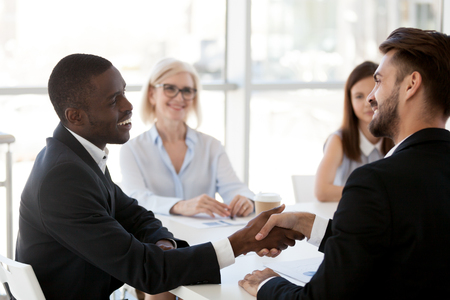 Caucasian businessman shake hand of black colleague greeting at briefing in office, diverse employees handshake introducing or getting acquainted at meeting, boss congratulate coworker with success Stockfoto