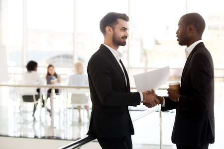 Diverse millennial colleagues handshake meeting in hallway having casual conversation, multiethnic male employees standing in office corridor shaking hands greeting, talking or chatting Stockfoto