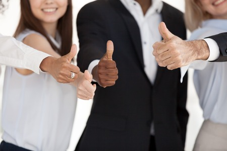 Close up of multiethnic happy workers or employees show thumbs up sign satisfied with career or company choice, smiling diverse business clients or customers gesture great positive experience