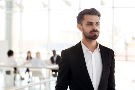 Focused Caucasian millennial employee look in distance thinking about new work opportunities, concentrated thoughtful businessman dreaming of future success, making plans. Business vision concept