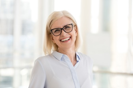 Portrait of smiling middle-aged businesswoman in glasses look in camera making headshot picture, happy mature female employee pose for picture in office, confident woman excited for new opportunities Stock fotó