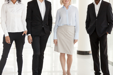 Feet of diverse office managers or employees standing in row posing for camera picture, legs of multiethnic confident motivated work team of men and women in formalwear in office or office hallway