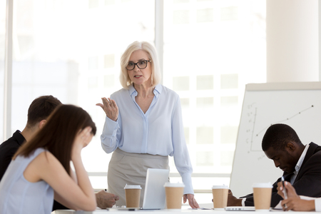 Angry mature businesswoman hold business briefing in office scolding young employees for bad work results, mad female boss lecture millennial workers or subordinates for failure at company meeting