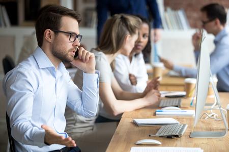 Impiegato maschio arrabbiato confuso che lavora al computer, risolve problemi aziendali al telefono, lavoratore pazzo parla al cellulare discutendo con cliente o cliente, uomo impegnato al pc con una conversazione seria sul cellulare