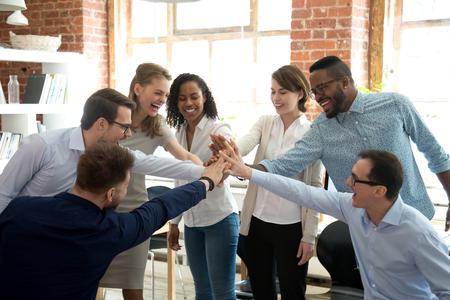 Los colegas multirraciales emocionados chocan los cinco involucrados en la actividad de trabajo en equipo en la reunión, los trabajadores diversos y felices unen sus manos celebran el éxito o ganan, muestran el espíritu de equipo y la unidad. Concepto de cooperación