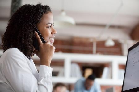 Sorridente dipendente di sesso femminile di colore comunica parlando al telefono lavorando al pc in ufficio, felice lavoratrice afroamericana risponde alla chiamata parlando con il cliente o chattando con gli amici sul posto di lavoro