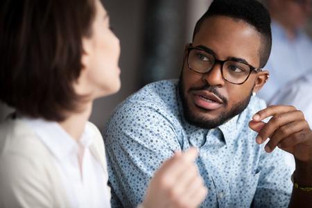 Close-up van multiraciale collega's die chatten of iets bespreken op kantoor, zwarte man spreekt met vrouwelijke collega die onderhandelt over een zakelijk project, een gesprek voert. Samenwerkingsconcept: