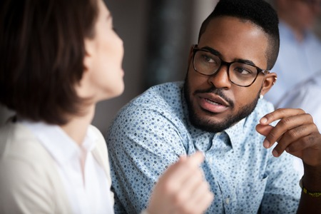 Zbliżenie na wielorasowe koleżanki i koleżanki rozmawiają lub rozmawiają o czymś w biurze, czarny mężczyzna rozmawia z koleżanką negocjującą projekt biznesowy, rozmawiając. Koncepcja współpracy
