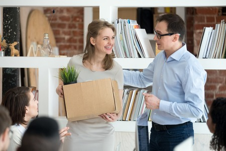 Businessman introduce excited female newcomer at corporate meeting to colleagues, male CEO presenting smiling employed woman or new employee with cardboard box in hands to coworkers. Hiring concept Stock Photo - 112480019