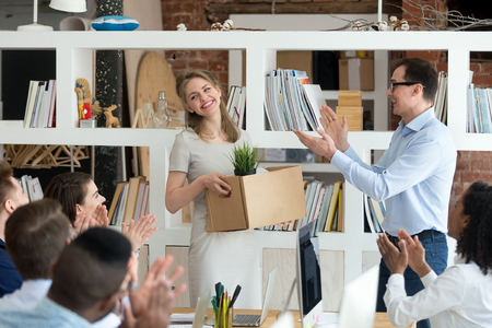 Happy male CEO and company workers applaud welcoming excited new female employee to team, smiling boss and colleagues clap acquainted with newcomer holding box at corporate meeting. Employment concept Stockfoto