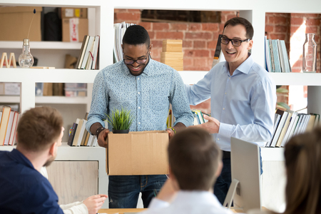 Excited male boss acquaint work team with African American male newcomer, shy black employee presented to coworkers on company briefing, businessman introduce newbie to colleagues