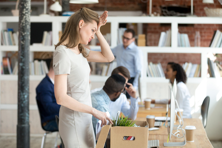 Frustrated female newcomer unpack cardboard box with personal belongings at workplace remembering something important, upset hired woman employee recall forgetting thing on first day in office