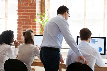 Back view of male teacher or trainer helping colleague with financial report working at computer in coworking space, businessman training young intern in office, giving assistance, explaining graph
