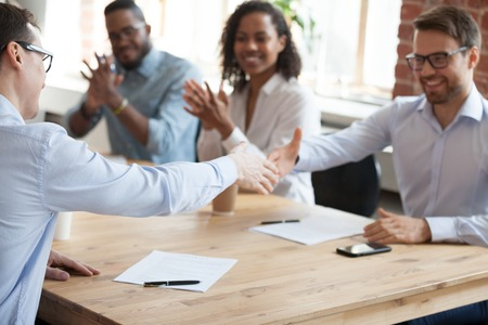 I soci d'affari sorridenti si stringono la mano dopo le trattative di successo in ufficio, i lavoratori maschi eccitati salutano la stretta di mano con l'occupazione, i dipendenti felici fanno conoscenza alla riunione. Concetto di partenariato