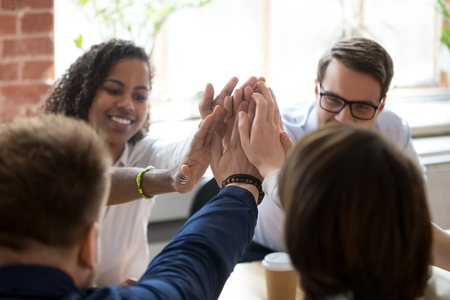 Close up of diverse colleagues give high five engaged in teambuilding activity at corporate meeting, multiracial employees join hands during briefing motivated to shared success and goal achievement