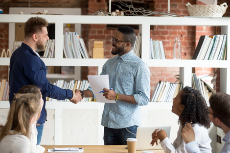 Smiling African American employer handshake millennial worker greeting with good work result during meeting, happy black CEO shake hand of Caucasian employee congratulating with success at briefing Stock Photo