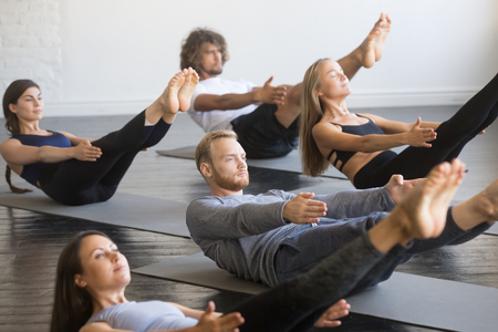 Group of young sporty people practicing yoga lesson, doing Paripurna Navasana exercise, boat pose, working out, indoor close up, studio. Healthy lifestyle concept Stock fotó