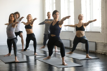 Group of young sporty people practicing yoga lesson, doing Warrior Two exercise, Virabhadrasana 2 pose, working out, indoor full length, students training in club, studio