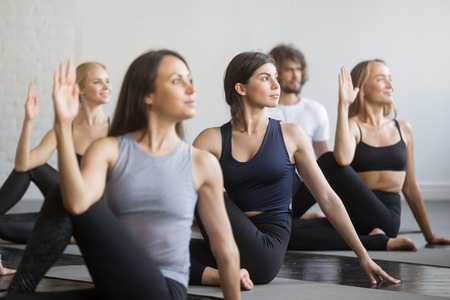 Group of young sporty people practicing yoga lesson, doing Ardha Matsyendrasana exercise, Half lord of the fishes pose, working out, students training, indoor