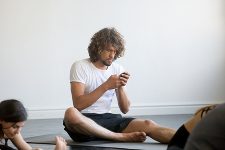 Bored young man sitting texting a message using his mobile phone, having a break while group of young sporty people practicing yoga lesson, sitting not working out, indoor close up, yoga studio club