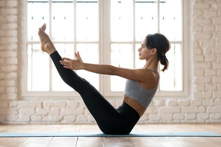 Jeune femme sportive séduisante pratiquant le yoga, faisant de l'exercice Paripurna Navasana, pose d'équilibre, faisant de l'exercice, portant des vêtements de sport, un pantalon noir et un haut, pleine longueur intérieure, studio de yoga blanc