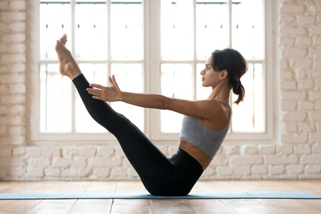 Young sporty attractive woman practicing yoga, doing Paripurna Navasana exercise, balance pose, working out, wearing sportswear, black pants and top, indoor full length, white yoga studio Stockfoto