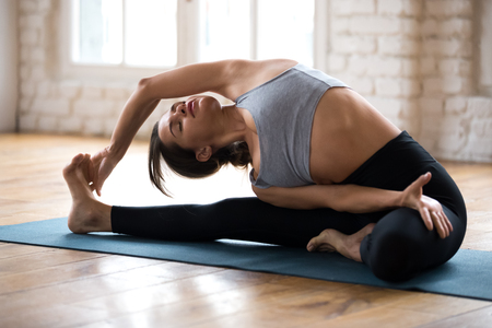 Young sporty woman practicing yoga, doing Revolved Head to Knee Forward exercise, Parivrtta Janu Sirsasana pose, working out, wearing sportswear, black pants and top, indoor full length, yoga studio Stock fotó