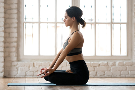 Young sporty attractive woman practicing yoga, doing Ardha Padmasana exercise, Half Lotus pose, working out, wearing sportswear, black pants and top, indoor full length, white yoga studio, side view
