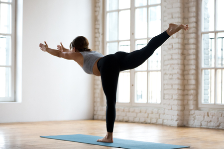 Young sporty attractive woman practicing yoga, doing Warrior III exercise, Virabhadrasana 3 pose, working out, wearing sportswear, black pants and top, indoor full length, white yoga studio, rear view Stock fotó