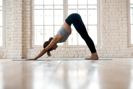 Young sporty woman practicing yoga, doing Downward facing dog exercise, adho mukha svanasana pose, working out, wearing sportswear, pants and top, indoor full length, white yoga studio
