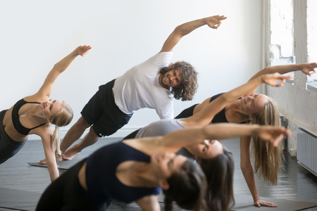 Group of young sporty people practicing yoga lesson, doing Vasisthasana exercise, Side Plank pose, working out, indoor close up, students training in club, studio