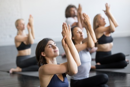 Group of young sporty people practicing yoga lesson, doing Cow Face exercise, Gomukasana pose, working out, indoor close up view, students training in club, studio 스톡 콘텐츠