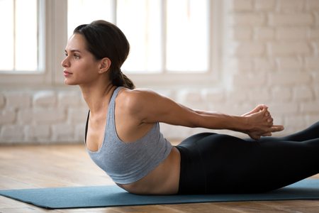 Young sporty woman practicing yoga, doing Double Leg Kicks exercise, Salabhasana pose, working out, wearing sportswear, pants and top, indoor close up, white yoga studio