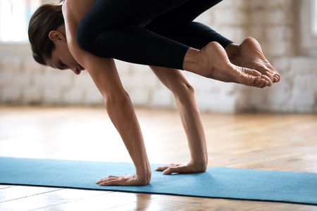 Young sporty attractive woman practicing yoga, doing Crane exercise, Bakasana pose, working out, wearing sportswear, pants and top, indoor close up, white yoga studio. Well being concept