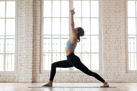Young sporty attractive woman practicing yoga, doing Warrior I exercise, Virabhadrasana 1 pose, working out, wearing sportswear, black pants and top, indoor full length, white yoga studio