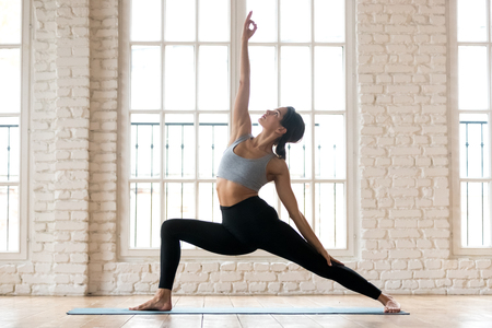 Young sporty attractive woman practicing yoga, doing Reverse Warrior exercise, Viparita Virabhadrasana pose, working out, wearing sportswear, black pants and top, indoor full length, white yoga studio Stock Photo
