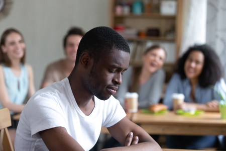 Groep diverse mensen zitten in café lachen spottend op zwarte man. Focus op apart zitten man voelt zich overstuur en ongelukkig, klasgenoten nemen hem niet mee naar hun bedrijf. Rassendiscriminatie concept Stockfoto