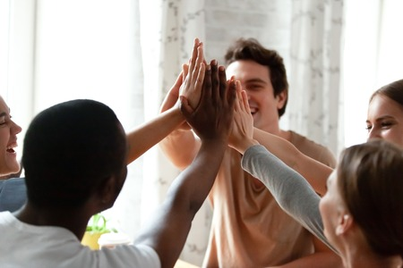 Diverse multiracial cheerful students giving high five greeting each other. Multi-ethnic millennial group of young people slapping palms sitting indoors. Gesture of celebration, friendship and unity Stok Fotoğraf
