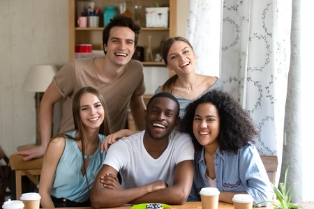 Happy multiracial people millennial girls guys sitting at desk smiling looking at camera, people spending time together are best friends. Friendship between diverse people and racial equality concept