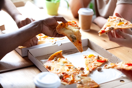 Diverse people having lunch eating fast junk food. Close up hands diverse multi-ethnic students holding pieces of pizza sitting at table in cafe. Unhealthy eating and meeting of best friends concept Stock Photo