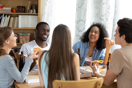 Multi-ethnic cheerful people enjoy time together, best friends diverse millennial girls and guys sitting around the table talking laughing have lunch eating pizza drinking craft beer in glass bottles Stok Fotoğraf