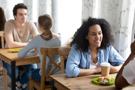 Multiracial young people youngsters sitting at table in cafe drinking coffee in paper cups, focus on mixed race smiling female. Diverse students spend free time during lunch at university cafeteria