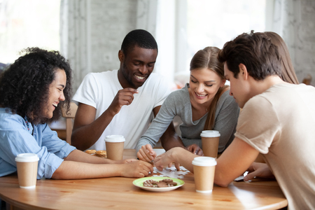 Diverse multiracial friends cheerful girls and guys drinking coffee having fun laughing assembling puzzle jigsaw sitting together at table in home or cafeteria. Teamwork and weekend activities concept Stock Photo - 112481269