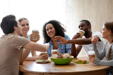 Diverse friends girls and guys sitting around table chatting having fun drink coffee in paper cups enjoy time together. Friendship between different race multinational young millennial people concept Standard-Bild